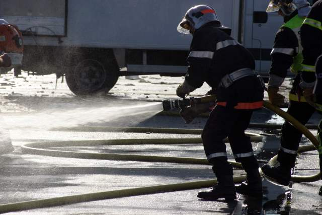 Fireman holding a firehose with water coming out.