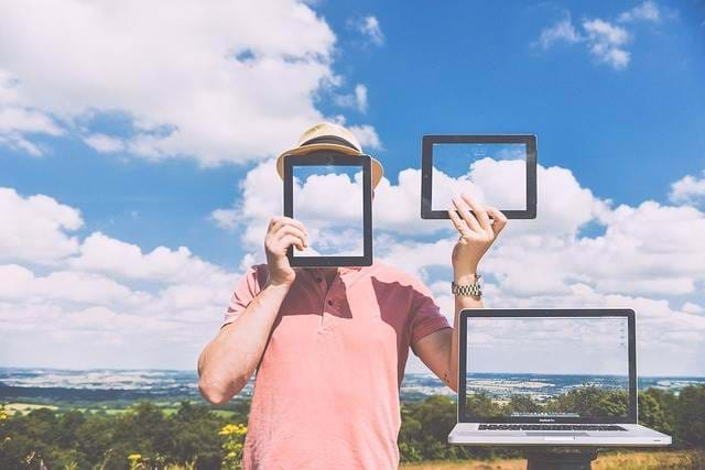 A view of the sky with a person holding up a tablet in front of their face with a cellphone and computer