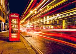Speedy Bus Flying By a London Telephone Booth