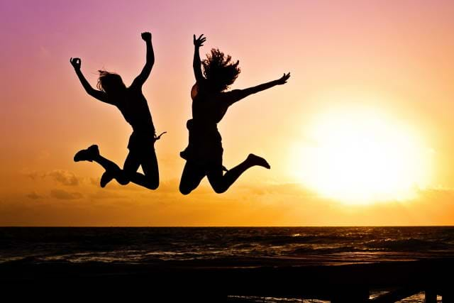 Two people jumping into the air