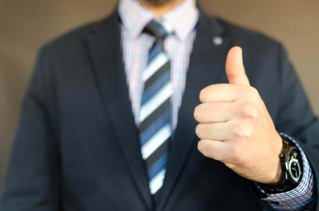 Man in a suit giving the thumbs-up