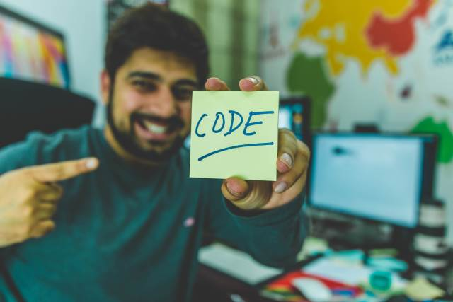 Man holding up post-it with Code written on it