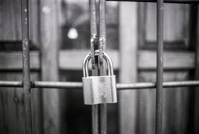 Black and White picture of padlock on a fence