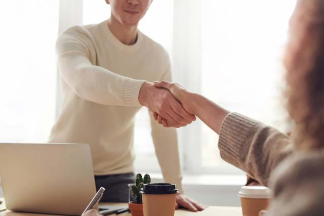 Man shaking hands in agreement with a woman