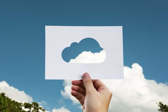 Man holding up a template of a cloud to the sky
