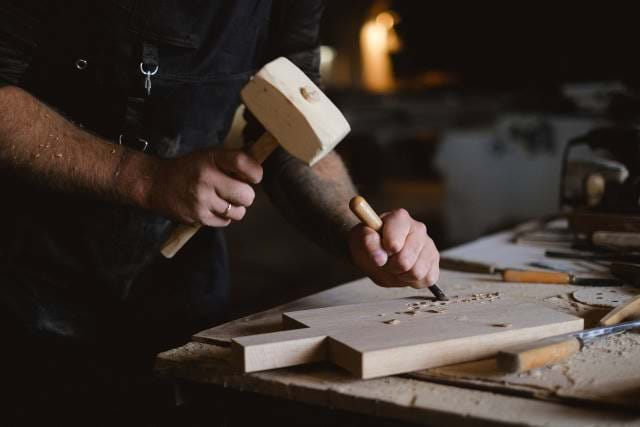 Man using a hammer to hit wood