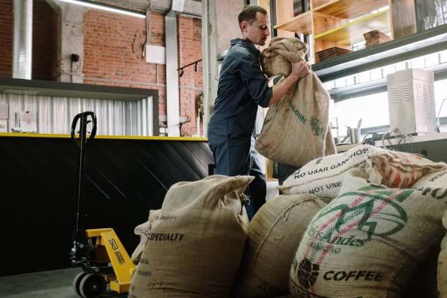 Man grabbing sacks of coffee beans.
