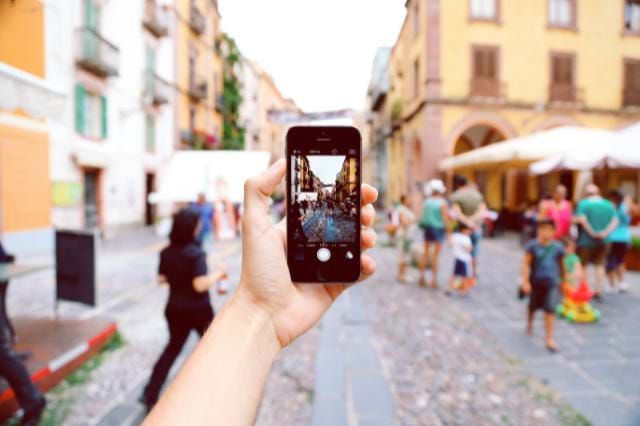 Man Holding Phone Taking A Picture Of Town
