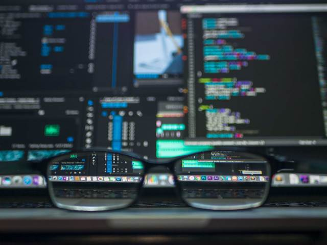 Glasses looking clearly at a fuzzy screen of code