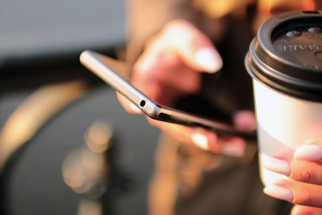 Man using his smartphone and drinking coffee