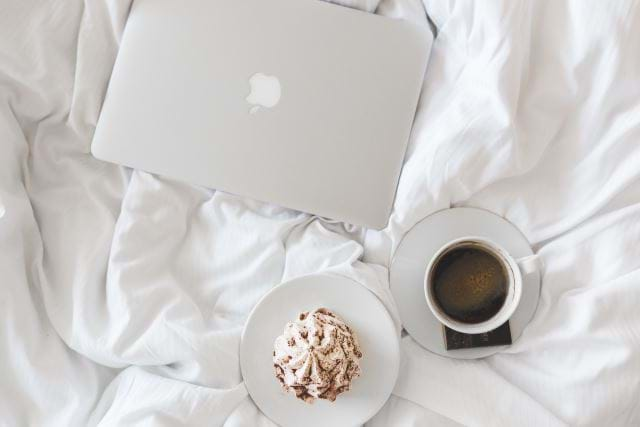 Apple computer, expresso, and breakfast on a bed
