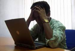 Man holding his head staring at a laptop