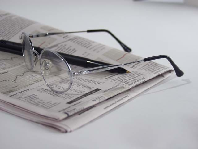 Picture of newspaper folder with a pen and glasses on it