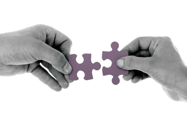 Two Jigsaw Pieces put together with two hands
