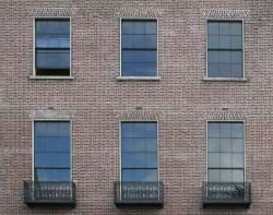 A grouping of windows on a brick wall